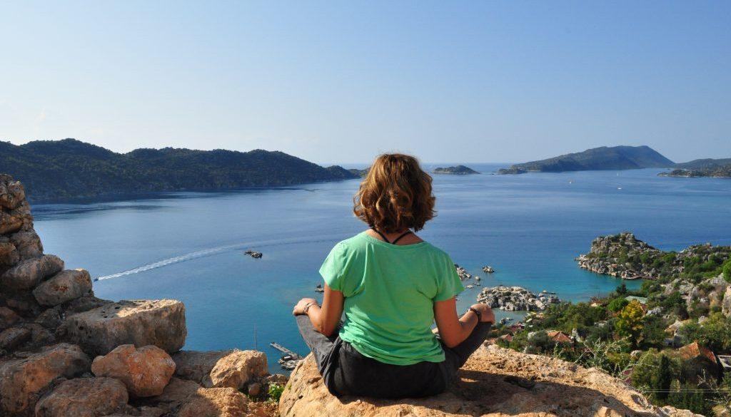 Frau sitzt in Meditationshaltung auf einem Felsen und blickt aufs Meer