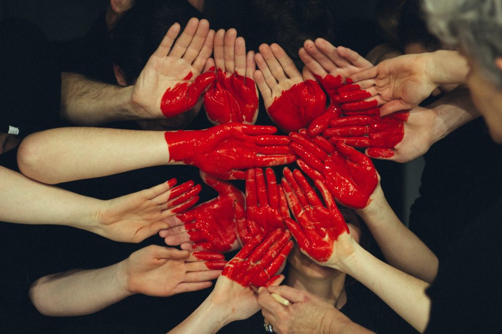Lots of hands coming together with a heart over the top