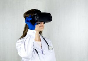 Person in a lab coat with a stethoscope around their neck looking through a Virtual Reality head set.
