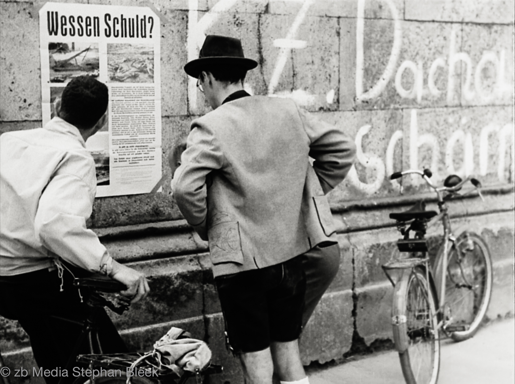 "Münchner Bürger lesen Plakat ""Wessen Schuld?"""